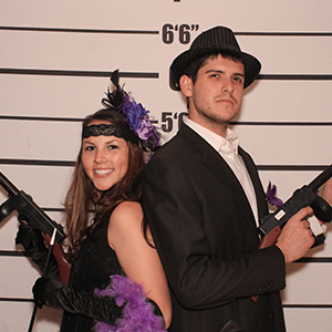 Boston Murder Mystery party guests pose for mugshots